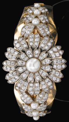 Natural pearl and diamond bracelet, 1940's. Of floral and foliate design set with natural pearls and circular-cut diamonds, inner circumference approximately 170mm, French assay and maker's marks, central flower jewel detachable. Via Sotheby's.