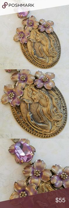 Handmade Nouveau Fairy Goddess pendant necklace Handmade  One of a kind  Nouveau Fairy Goddess pendant on a brass stamping Accented with lavender vintage metal flowers and a gorgeous large glass amethyst colored stone  Antique gold chain Toggle closure Handmade Jewelry Necklaces