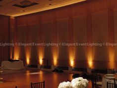 Amber Uplighting will wash the walls with candle lit color in the all white atrium space