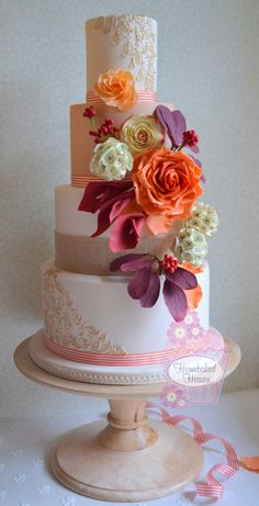 """Wedding cake decorated with oversized rose in burnt orange, """"Double Delight"""" hybrid tea rose, cotinus foliage, scabiosa seed heads, calla lilies and berries... plus leaves in gilded royal icing piping for a touch of opulence... a riot of autumnal colour...."""