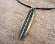 This necklace features a surfboard pendant that I made using tigerwood with blue green/teal curly maple. The curly maple was infused with blueish green resin using a vacuum chamber which draws the resin into the woods center giving it a very unique look. Almost like a wave is moving through
