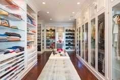 This closet has two long, button-tufted benches with a table in between that houses a phone and several small decor items. All hanging space is enclosed behind glass doors, while glass and wood shelving houses layering tops, sweaters, purses and shoes.