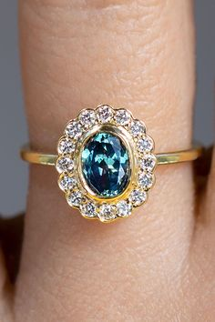 This glimmering ocean colored sapphire hails from Montana, USA. Surrounded by a halo of recycled vintage round brilliant cut white diamonds to form an ethereal low-profile one of a kind ring. A modern ethically sourced American Treasure upgrade of a classic and much-loved design. Sapphire Diamond, Diamond Rings, Diamond Engagement Rings, Diamond Cuts, Budget Friendly Engagement Rings, Vintage Diamond, Jewelry Accessories, Mystery Dinner, Bling