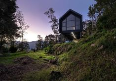 See DH House, the prefab home in Taiwan from Urdaneta Zeberio, a low-budget residence that embraces an adaptive spirit. House On Stilts, Hot And Humid, Green Valley, Mountain Homes, Prefab Homes, Architecture Photo, Large Windows, Simple House, Minimalist Home