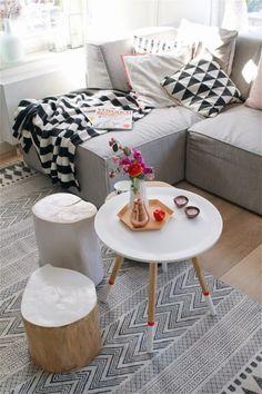 Ciekawe dodatki ożywiają łagodną aranżację salonu. Okrągły stolik z białym blatem i białymi zakończeniami drewnianych...
