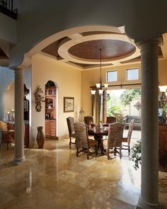 Vaulted ceilings and arched doorways make this mediterranean home seem grand and resort-like. Underneath the antique chandelier sits simple wooden dining table with boldly pattern chairs and red placemats.