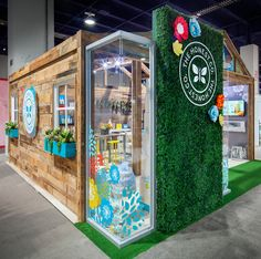 Just lovely! The Honest Co. booth with flower wall, pallet wall and graphic clings!