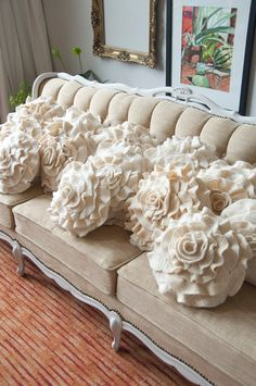 pillows are so pretty! take wide strip of fabric, ruffle by pulling thread tight, then roll and tack, roll and tack until you create a flower.