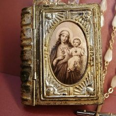 What a fabulous old rosary box that hangs from a vintage glass rosary ( less the crucifix) ..There is a faux mother of pearl  rosary inside. The necklace is made of old  crystal  rosary beads that are
