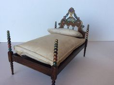 Rare Tynietoy Spanish bed with beaded posts and headboard with painted urn and cascading flowers flowing out of the urn and down the sides. The urn rests on a scalloped formed headboard with cut outs below. The painting is beautiful and very decorative, to say the least! There are slight variations in the decoration of the Spanish bed headboards.