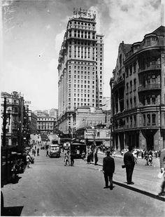 Fotografia da Avenida São João tomada da esquina da Rua Formosa em direção à Praça Antônio Prado, por volta do ano de 1933.  Do lado esquerdo, o prédio da Delegacia Fiscal e o Martinelli.
