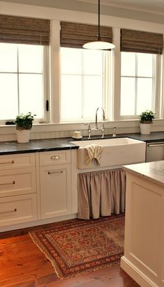 neutral below sink curtain breaks up the hardness of the cabinets; love the farmhouse sink