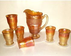 This is a Fenton Glass Co rare pattern named SCALE BAND, made between 1908 - 1930 in iridescent Marigold colored Carnival glass. Truely a rare find for an entire set in this color and pattern! You can verify pattern specifics and rarity on reputable carnival glass website Does come with some flaws but no chips or cracks found on pitcher or tumblers. Do expect some light scratches, air bubbles, and discolored spots on one glass, although normal characteristic for antiques. The dark spots…
