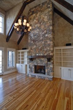 Beautiful floor to ceiling stone fireplace with farmhouse mantle, vaulted ceiling with exposed beams and custom built ins beside the fireplace. Gorgeous living room!