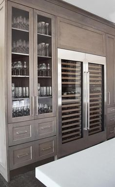 Amazing kitchen features a built-in glass-front china cabinet situated next to side by side glass-door wine coolers atop a black staggered tiled floor.