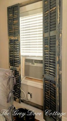 Antique shutters affixed to wood frame, create a screen cover for window and ac hvac unit.