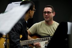 U.S. Air Force Tech. Sgt. Alex Nikiforoff, right, a U.S. Air Forces in Europe Band guitarist, helps Vicenza's Donald Neal with a section of guitar music during the DODEA-Europe Jazz Seminar at Ramstein Air Base, Germany, on Tuesday, Jan. 10, 2017. Volunteers from the USAFE band helped mentor student musicians as well as taking care of many of the seminar's logistics. Michael B. Keller/Stars and Stripes