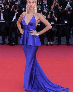 Hailey Baldwin Is Radiant In Plunging Royal Purple Gown At Cannes  -Hailey Baldwin almost had a little Cinderella moment on the Cannes Film Festival red carpet, with her heal getting caught on her stunning deep purple peplum gown. The model kept her composure and oh-so-gracefully adjusted her gown before continuing to rock the carpet!