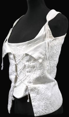 Wedding corset | Vivienne Westwood | Great Britain, 1995 | Boned cotton and zip | White cotton piqué front over bodice laced across the front and inner bodice of ribbed white cotton boned. Side panels of white mesh. Lace string fastens shoulder straps at front, with zip closure down the back. Imitates 18th century stays in cut | VA Museum, London