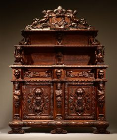 An Italian Baroque style walnut sideboard, Late 19th century, the pierced crest centering a figure of Neptune, flanked by female terms over two graduated shelves suspended by mermen, griffins and grotesque masks above an outset case fitted with a pair of drawers over a pair of doors enclosing a shelf, flanked by further grotesque masks and figural terms, on scrolled bracket feet.