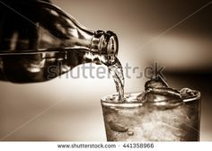 Pouring soda water from bottle into glass in sepia tone.Toned image,soft focus,film noir style.