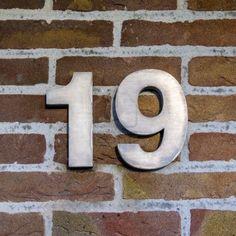casa de tres dimensiones de metal número diecinueve en una pared de ladrillo Foto de archivo - 14692092