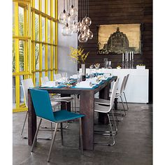 mix of elements: rustic table, modern white chairs, traditional art, bright color...