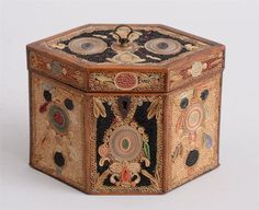 GEORGE III ROLLED PAPER-MOUNTED SATINWOOD TEA CADDY -  Of oblong hexagonal cross section with black and fawn-ground reserves enclosing concentric ovals and petal clusters, stained in green and red, later velvet-lined interior. 5 1/8 x 7 3/8 in. Provenance: Michael Lipitch Antiques, Fulham Road, London.   The Collection of Sallie Blumenthal, NY
