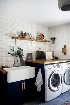 Simple but beautiful Laundry Room with Subway Tile, a Farm Sink, Black Cabinets and warm wood countertops.