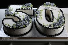 "Grey Roses 50 #86Milestones  Shaped as the number ""50"", this cake is iced in buttercream and trimmed in black. The numbers are decorated with grey roses and accented with sparkly gems."