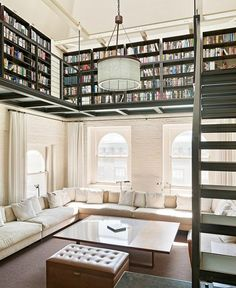 Love this lofty space...the sitting space that wraps all around below.. with all the windows and the bright feel..and the library of books up stairs. Brick & windows are, of course, amazing.