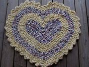 Rag rug in heart shape crocheted with buttercup yellow and floral print