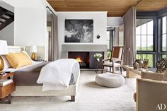 Neutral Bedroom with Large Windows, Wood-Paneled Ceiling and Custom Art above the Fireplace