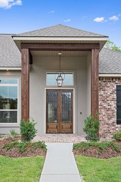 A custom front porch featuring rustic wood beams, lovely double doors, and a charming Bevolo gas lantern.