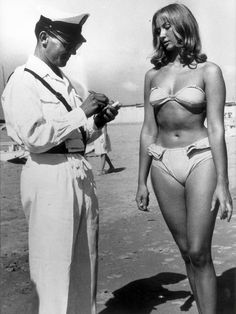 A police officer issuing a woman a ticket for wearing a bikini on a beach at Rimini, Italy in 1957