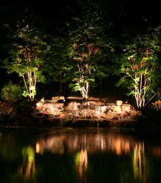 Add up-lighting to the trees in your backyard.  This poolside spot has lights that illuminate the waterfalls, too.
