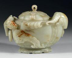 IMPORTANT POT couvert en néphrite céladon tachée de rouille, sculpté en haut-relief d'une tête de bélier d'un côté et de l'autre, d'un dragon stylisé et ailé formant anse et supportant un anneau mobile. Sur le côté, quatre frises de vagues. Le couvercle est sculpté de pétales de fleurs surmontées d'un bourgeon. Le talon est formé par une feuille de lotus. Chine, époque Qianlong, XVIIIe siècle. (Deux petits éclats à la tête de dragon et égrenure au couvercle). Longueur: 16,5 cm Provenance…
