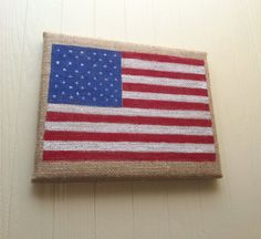 Show your patriotism with this American Flag painted on tan burlap. It is a great addition to any American décor you may have in your home.