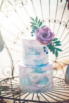 Cool-toned color palettes can make you feel calm and relaxed on a hot summer day. This watercolor wedding cake uses shades of white, silver, purple, and sky blue to create a delicious (and refreshing) design.
