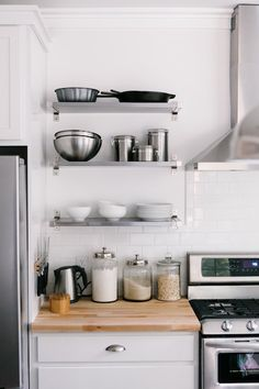 White kitchen with stainless steel fridge beside Ikea EKBY MOSSBY/EKBY BJÄRNUM Wall Shelves in place of upper cabinetry over a white subway tiled backsplash and Ikea Beech Numerar Butcher Block counters which frame a stainless steel range with stainless range hood.