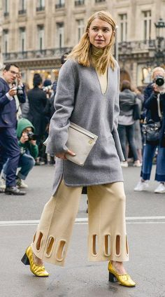 Pernille Teisbaek in a cream turtleneck, gray wool tunic sweater, cream culottes and gold Celine ballet slippers