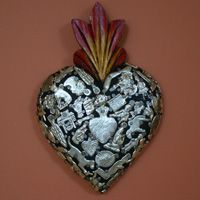 wooden heart covered with milagros