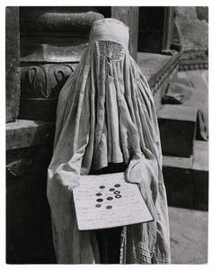 Because the laws of Islam prohibit women from speaking loudly, this professional Muslim female beggar is holding a card, which has a message written in Urdu saying she is a widow with two children and no one to support her, Delhi], 1946  photo by Margaret Bourke-White