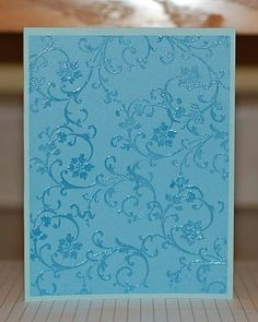 By Lynn Mangan. Stamp a background stamp with VersaMark and heat emboss in clear powder. Makes a great background!