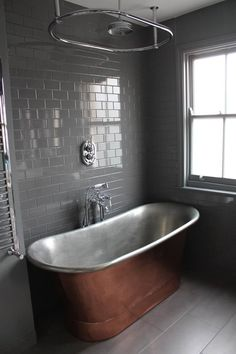 Our copper bath is the star of this bathroom. Tub from The Cast Iron Bath Company. Retro Metro tiles by Fired Earth. Walls and woodwork in Plummet by Farrow and Ball