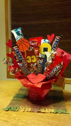 Basketball and snickers inspired candy bouquet. Filled with jumbo candy bars, movie sized boxed candy, rice crispie treats, basketball and heart cut outs and stacked mini snickers.