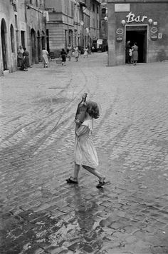 Little girl carries a magnum of wine home.  Rome, 1952;  photo by henri cartier-bresson/magnum photos