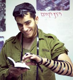 Handsome IDF soldier smiles while reading Psalms, wrapping Teffillin.