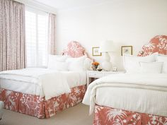 Guest bedroom, two full beds, shared bedside table with shelves and drawers for storage.