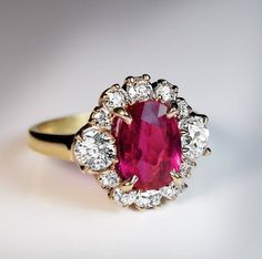 Vintage silver topped 18K gold ring is centered with an oval natural unheated pink-red 2.71 ct ruby from Burma (Myanmar). The ruby is framed by bright white (F-G color) old mine cut diamonds (estimated total weight 1.25 ct).